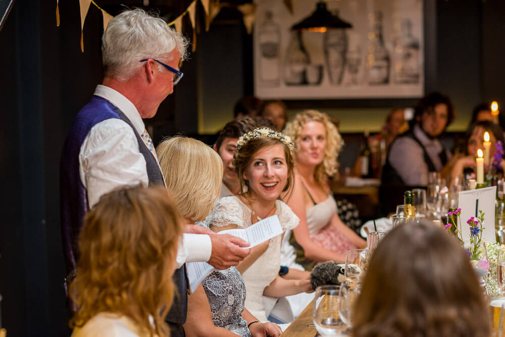 Bride laughing at father of the bride speech