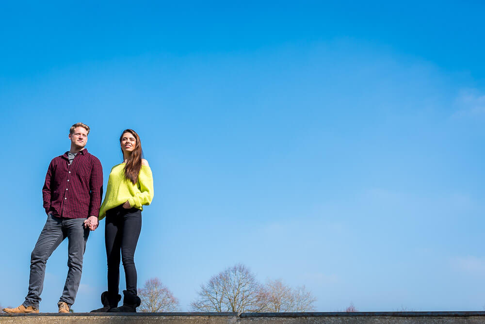 Couple holding hands with blue sky in background