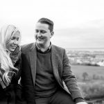 couple smiling on hill overlooking city