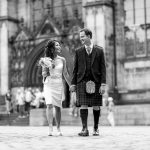 Bride and groom holding hands and smiling whilst walking
