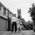 couple holding hands in cobbled street