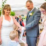 bride, groom, flower girl and page boy tying the knot at wedding