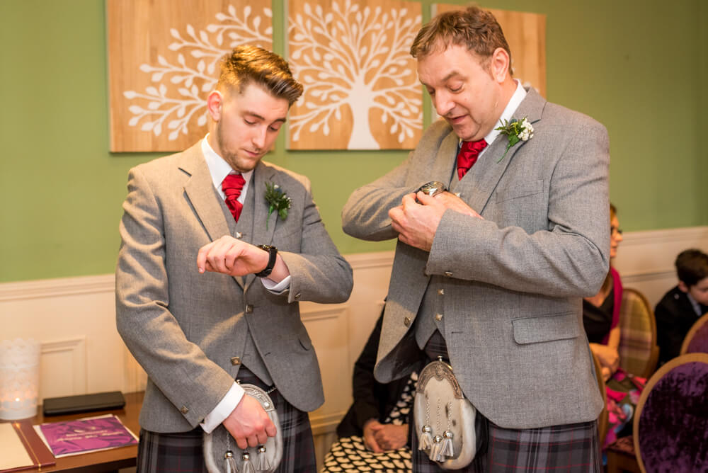 Groom and best man checking their watches