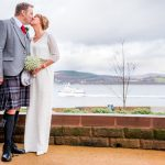 Bride and groom kissing with boat in the background