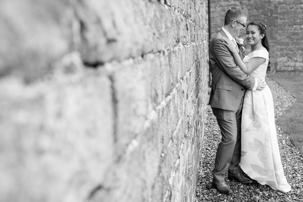 Bride and Groom standing against wall