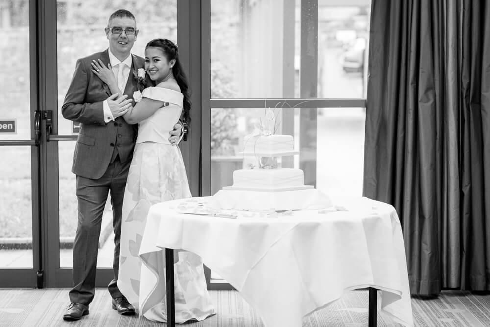 Bride and groom next to wedding cake