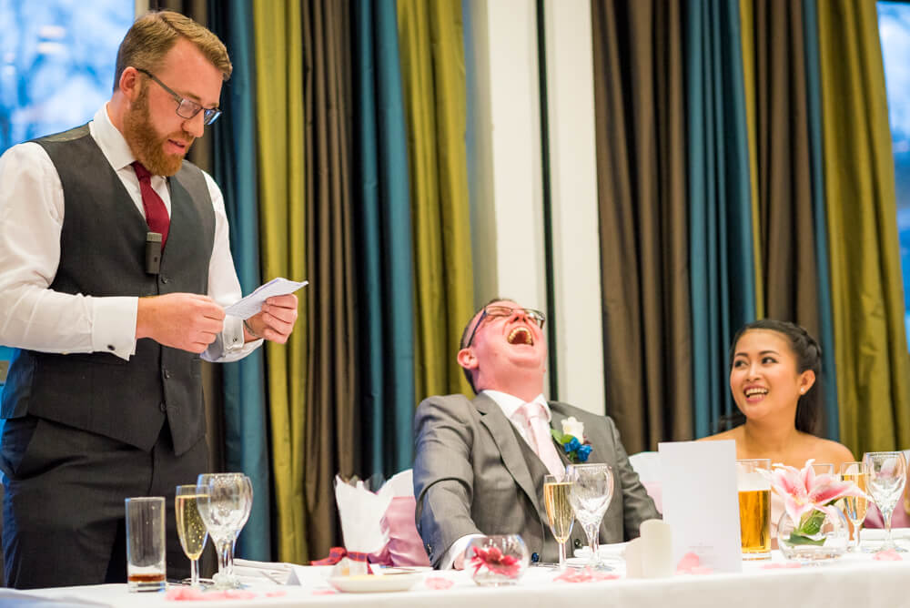 Groom laughing at best mans speech