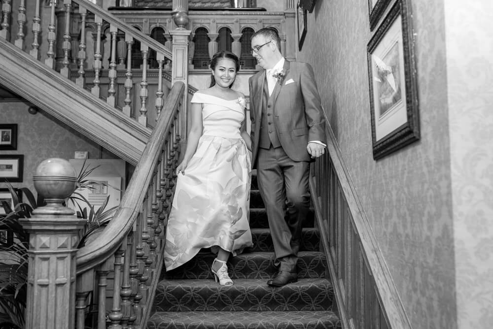 Bride and Groom walking down staircase