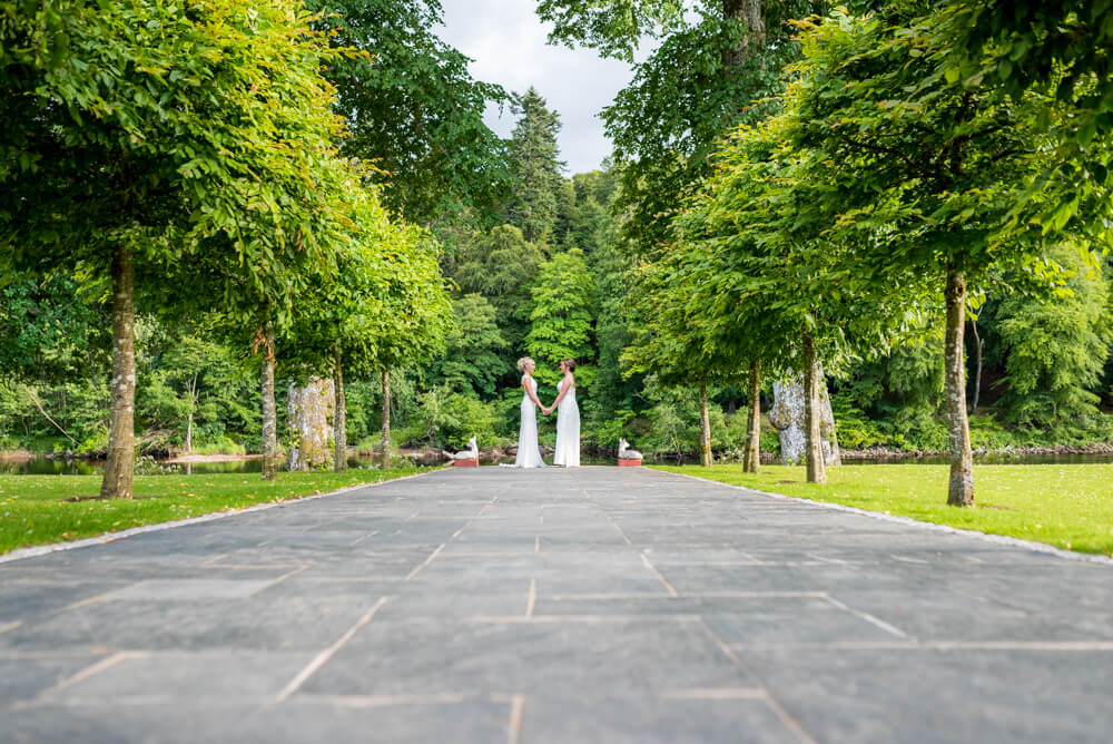 Bride holding hands at end of path at Dunkeld House Hotel