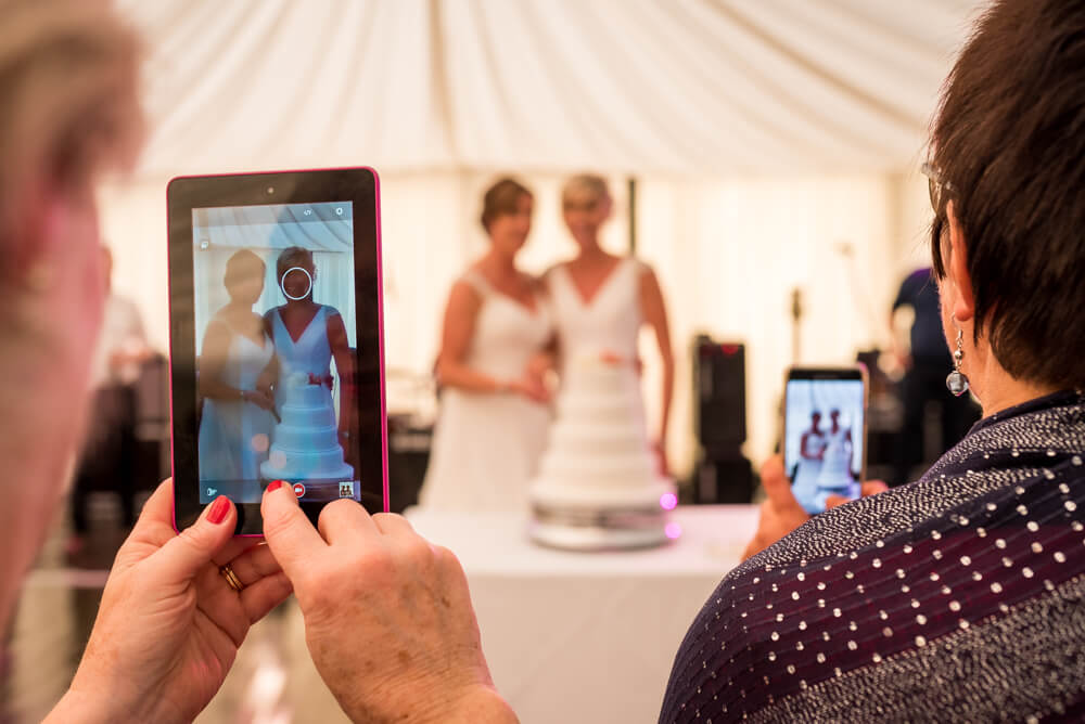 Brides cutting wedding cake through wedding guests phone