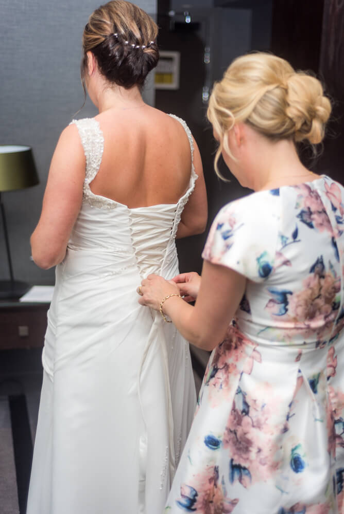 Bridesmaid putting on brides dress
