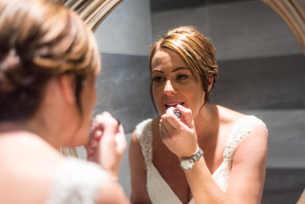 Bride doing her lipstick in the mirror