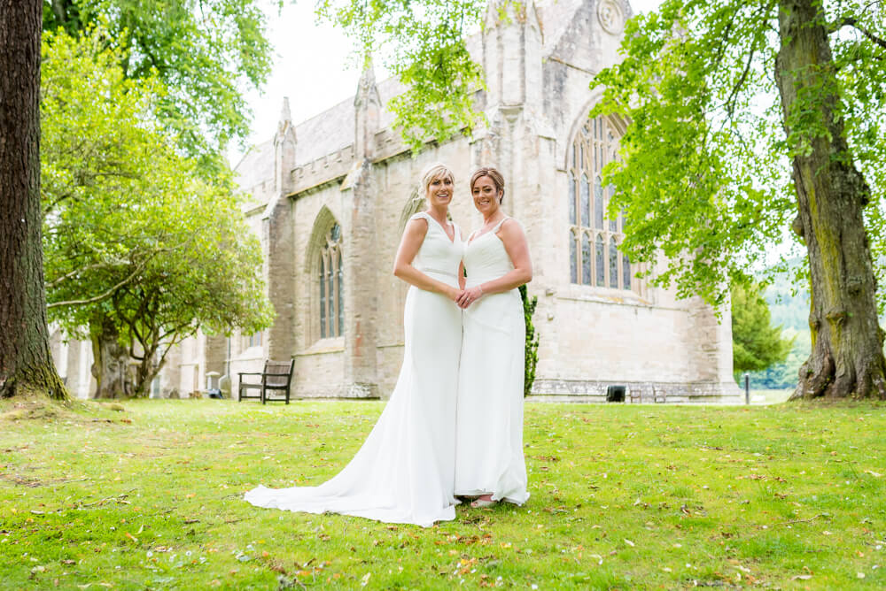 Brides holding hands with church in background