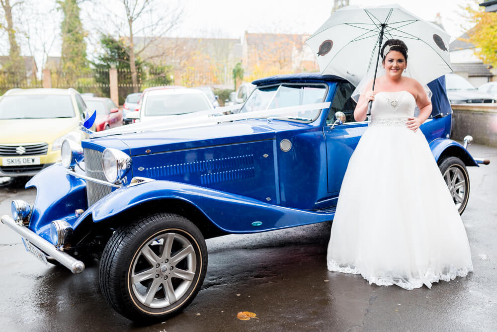 Bride standing next to stunning wedding car