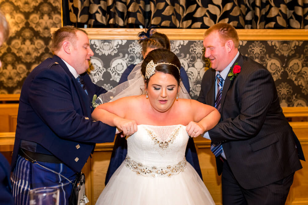 Groom and family help bride with her wedding dress