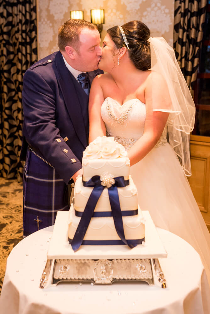 Bride and groom cutting cake and kissing at The Parkville Hotel