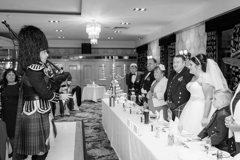 Piper playing his bagpipes in front of the top table