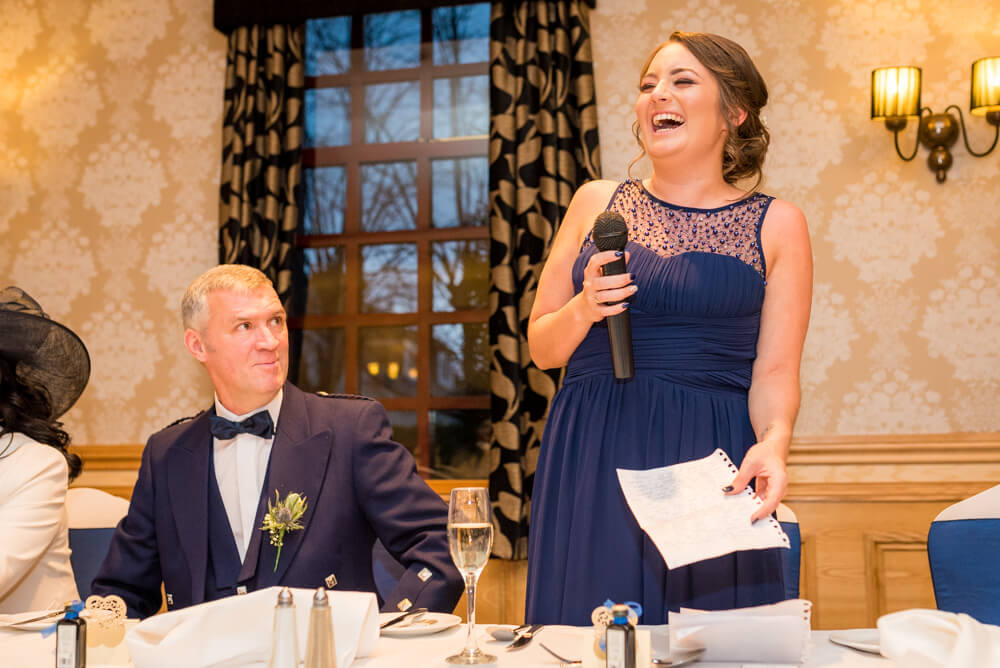Bridesmaid laughs during wedding speeches