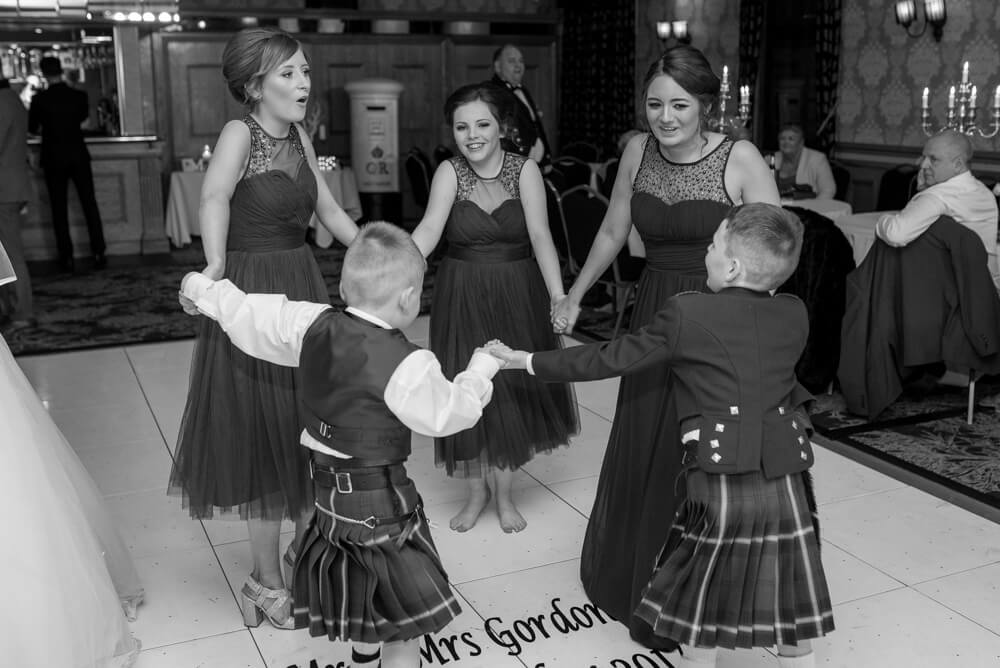 Bridesmaid and pageboys dancing in a circle