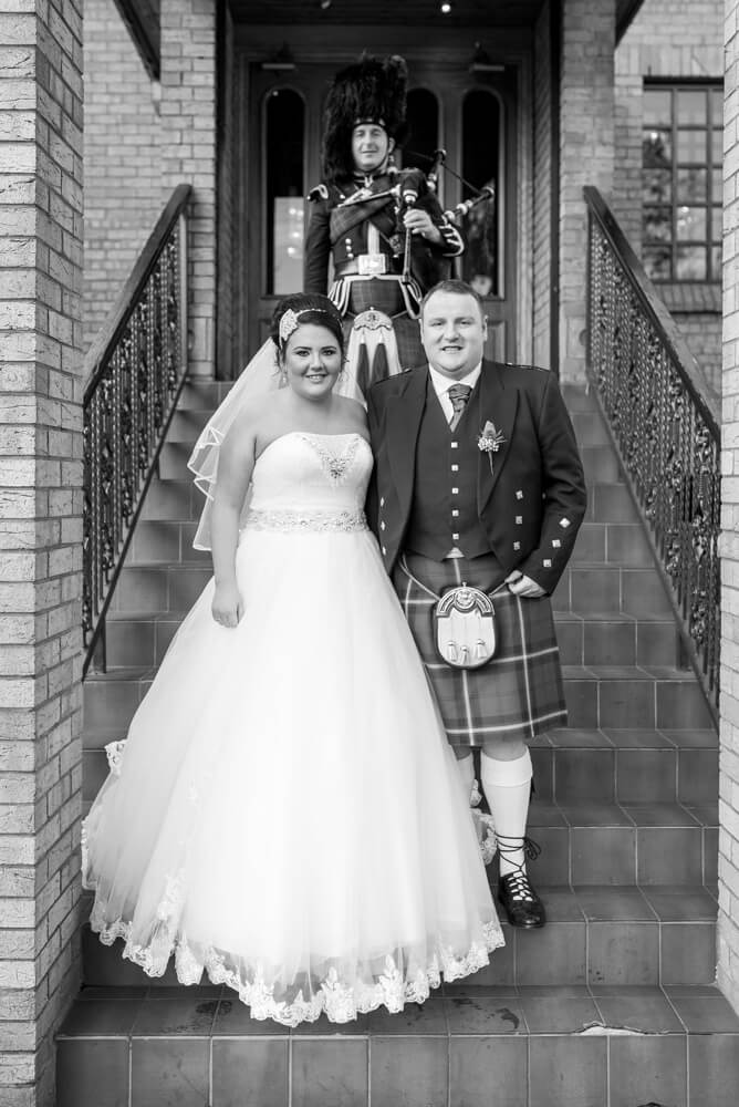 Bride and groom with piper outside the Parkville Hotel