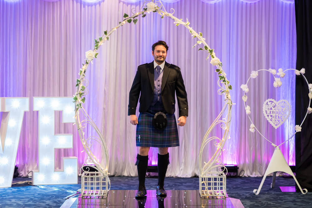 Groom in kilt walks down catwalk at wedding show