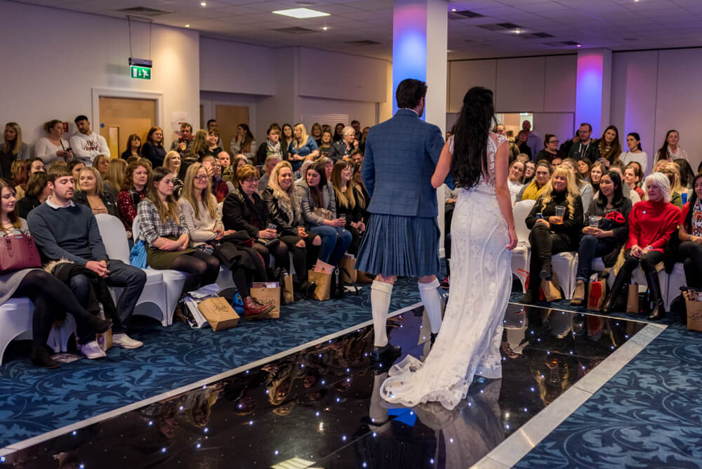 Bride and groom walking down catwalk at Murrayfield Stadium
